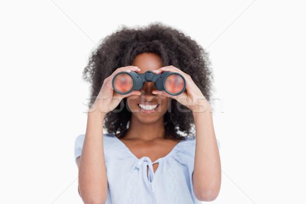 Jeune femme cheveux bouclés regarder jumelles blanche visage Photo stock © wavebreak_media
