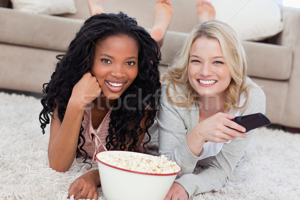 Two women lying on the ground with popcorn are smiling at the camera and have a TV remote Stock photo © wavebreak_media
