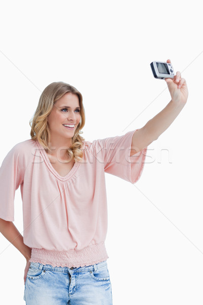 A woman is talking a photo of herself with her digital camera against a white background Stock photo © wavebreak_media