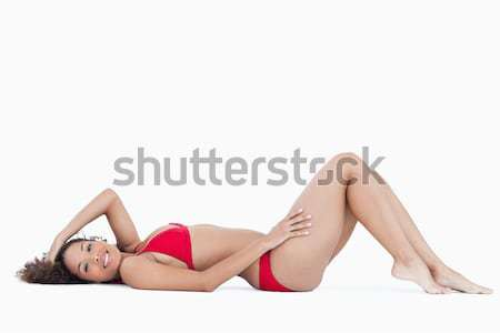 Attractive woman in swimsuit lying down against a white background Stock photo © wavebreak_media