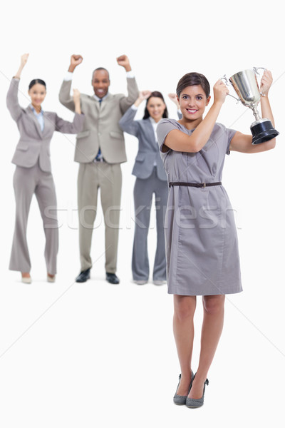Picture centered on woman smiling and holding up a cup with co-workers raising their arms in the bac Stock photo © wavebreak_media