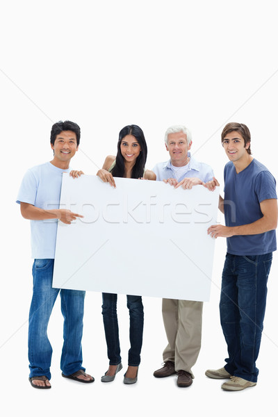 Stock photo: Smiling people holding and showing a big sign against white background