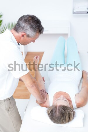 Physiotherapist massaging the lower part of the back of his patient in a room Stock photo © wavebreak_media