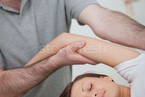 Osteopath holding the arm of a woman while massaging her body in a room Stock photo © wavebreak_media