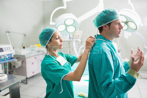 Side view of a nurse helping a surgeon in an operating theatre Stock photo © wavebreak_media