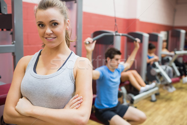 Smiling female trainer with arms crossed in fitness studio in gym Stock photo © wavebreak_media