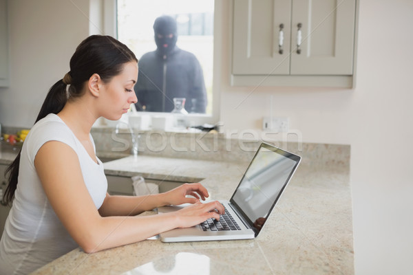 Woman using a laptop in the kitchen with burglar standing at the window Stock photo © wavebreak_media