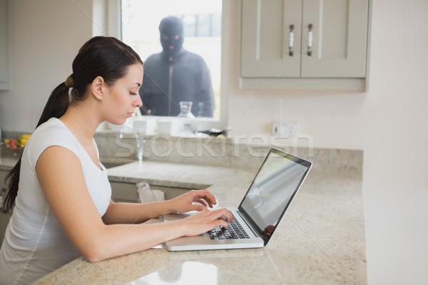 Donna utilizzando il computer portatile cucina scassinatore piedi finestra Foto d'archivio © wavebreak_media