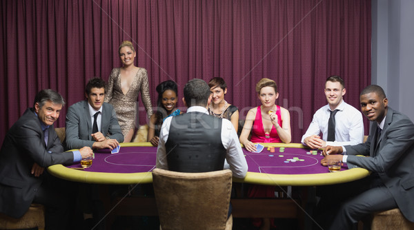 Smiling group sitting around poker table in casino Stock photo © wavebreak_media