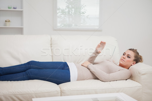 Woman lying on the sofa and relaxing while viewing a pane as a tablet pc Stock photo © wavebreak_media