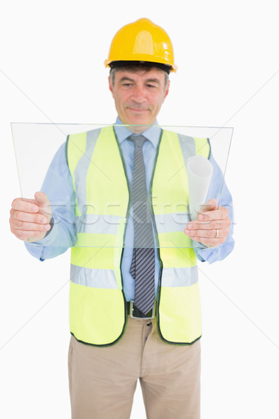 Smiling architect holding a pane and viewing it Stock photo © wavebreak_media