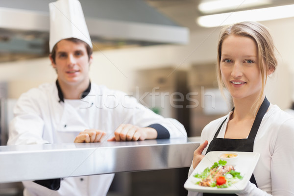 Waitress holding salmon dish smiling with chef in the kitchen Stock photo © wavebreak_media