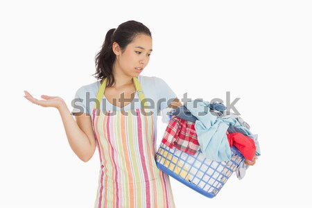 Quizzical looking young woman in apron looking at basket full of dirty laundry  Stock photo © wavebreak_media