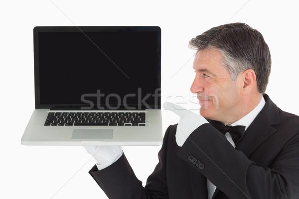 Waiter holding and pointing to laptop  Stock photo © wavebreak_media