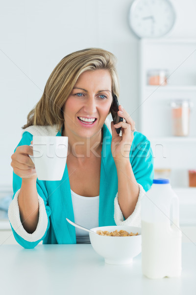 Smiling woman in dressing gown calling during her breakfast Stock photo © wavebreak_media