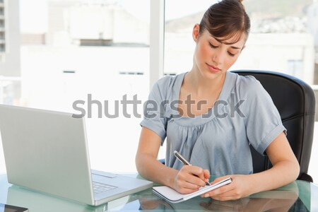 Stock photo: Female executive using laptop as she holds coffee cup at desk