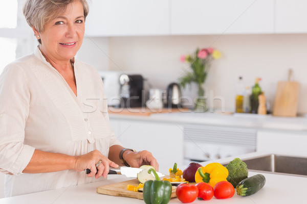 Elderly woman cutting vegetables on a cutting board with a smile Stock photo © wavebreak_media