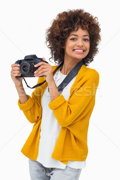Smiling girl holding digital camera Stock photo © wavebreak_media