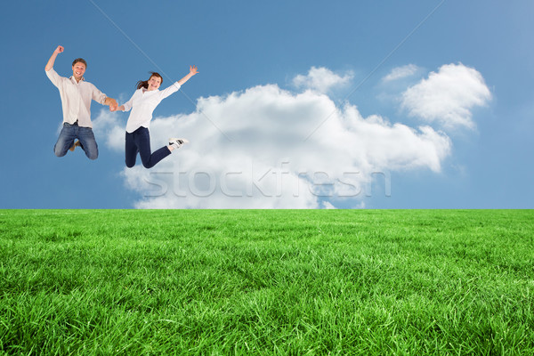 Composite image of couple jumping and holding hands Stock photo © wavebreak_media