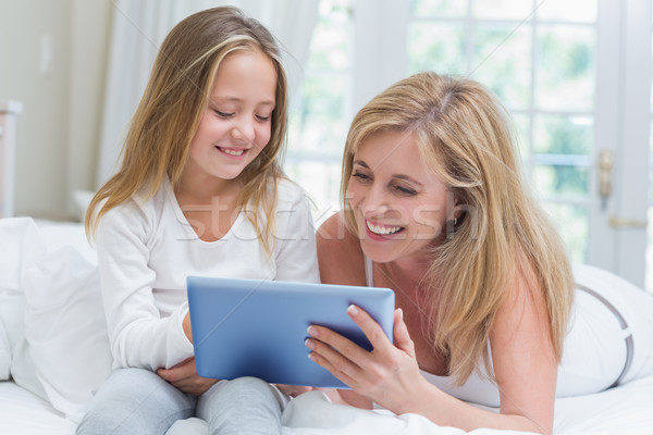 Stock photo: Mother and daughter using tablet pc in the bed