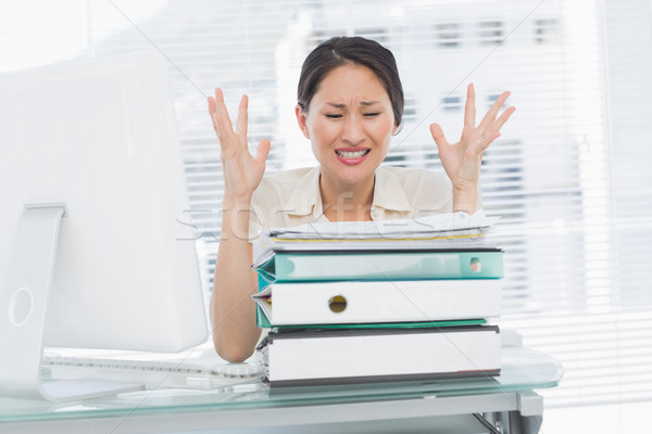Angry businesswoman shouting with stack of folders at desk Stock photo © wavebreak_media