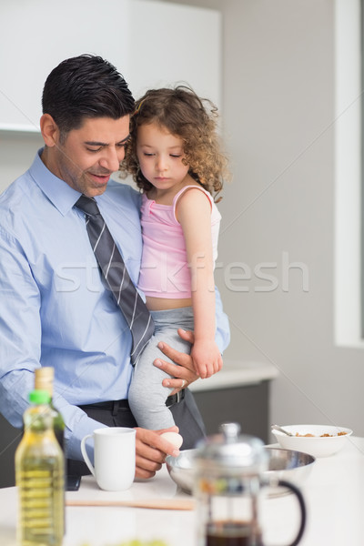 Well dressed father carrying his daughter while preparing food Stock photo © wavebreak_media