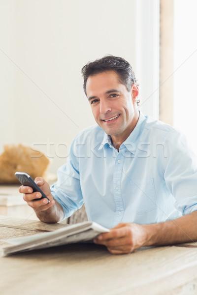Glimlachend toevallig man krant mobieltje keuken Stockfoto © wavebreak_media