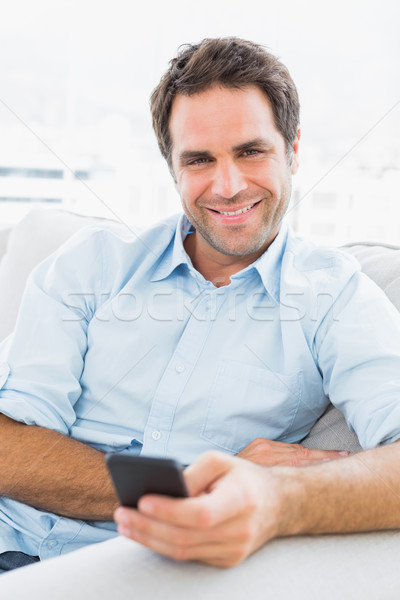 Cheerful man sitting on the couch sending a text Stock photo © wavebreak_media