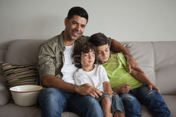Father and sleepy sons with popcorn bowl watching tv in living r Stock photo © wavebreak_media