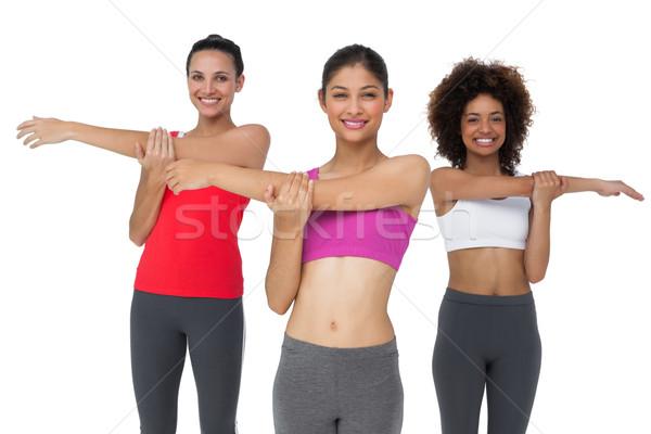 Portrait of three sporty young women stretching hands Stock photo © wavebreak_media