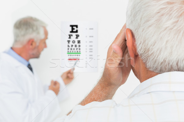 Pediatrician ophthalmologist with senior patient pointing at eye Stock photo © wavebreak_media