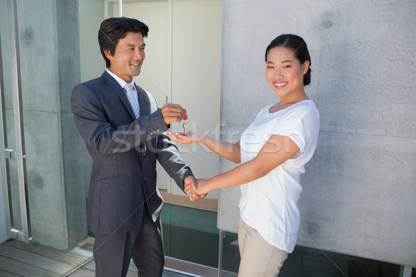 Stock photo: Estate agent giving house key to buyer