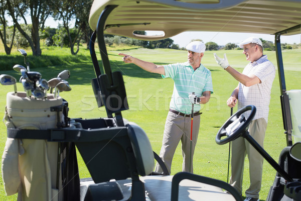 Golfing friends standing beside their buggy looking around Stock photo © wavebreak_media