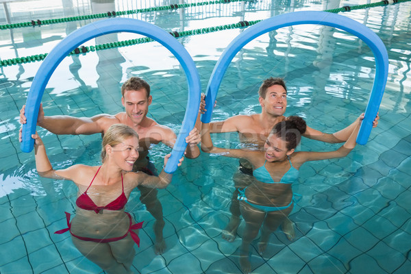 Fitness class doing aqua aerobics with foam rollers Stock photo © wavebreak_media