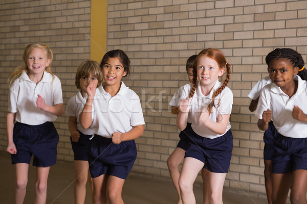 Cute pupils warming up in PE uniform Stock photo © wavebreak_media