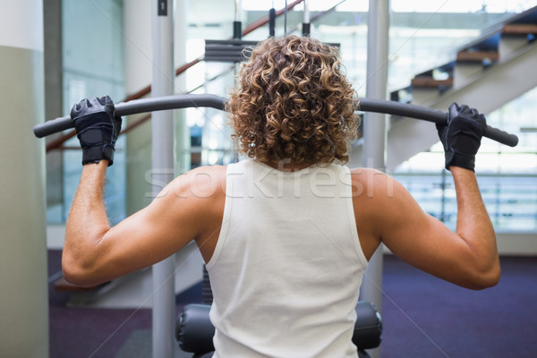 Rear view of a man exercising on a lat machine Stock photo © wavebreak_media