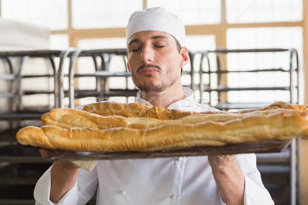 Baker smelling freshly baked baguettes Stock photo © wavebreak_media