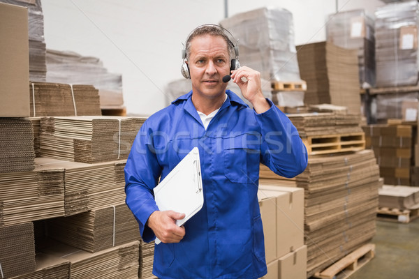 Serious warehouse worker using headset Stock photo © wavebreak_media