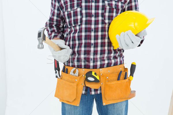 Handyman holding hard hat and hammer Stock photo © wavebreak_media