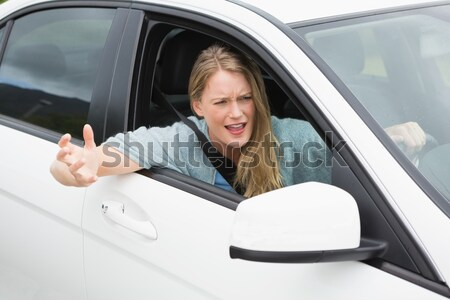 Woman gesturing thumbs down holding a learner driver sign Stock photo © wavebreak_media