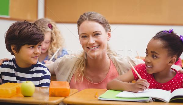 Teacher and pupils working at desk together Stock photo © wavebreak_media