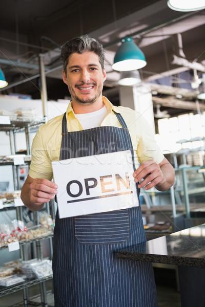 Attractive worker holding open sign Stock photo © wavebreak_media