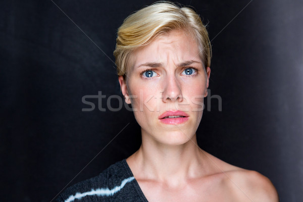 Anxious blonde woman looking at camera Stock photo © wavebreak_media