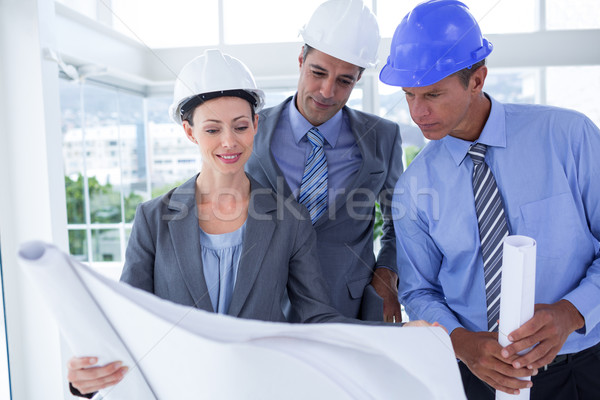 Businessmen and a woman with hard hats and holding blueprint Stock photo © wavebreak_media