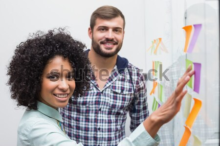 Stock photo: Casual business team looking at sticky notes
