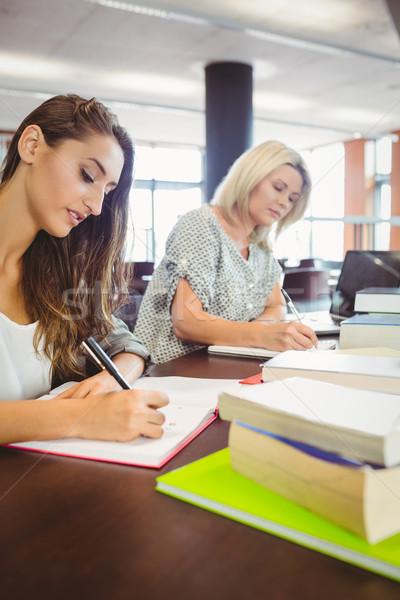 Matures females students writing notes at desk Stock photo © wavebreak_media