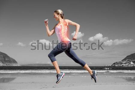 Highlighted back bones of jogging woman on beach Stock photo © wavebreak_media