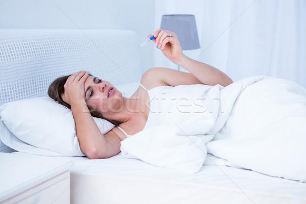 Enfermos mujer mirando termómetro casa dormitorio Foto stock © wavebreak_media