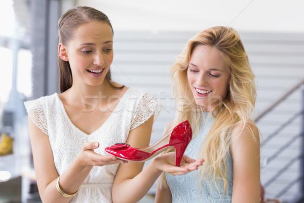 Happy women looking at a heel shoe Stock photo © wavebreak_media