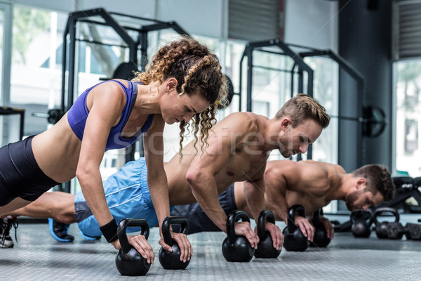 Three muscular athletes on a plank position Stock photo © wavebreak_media